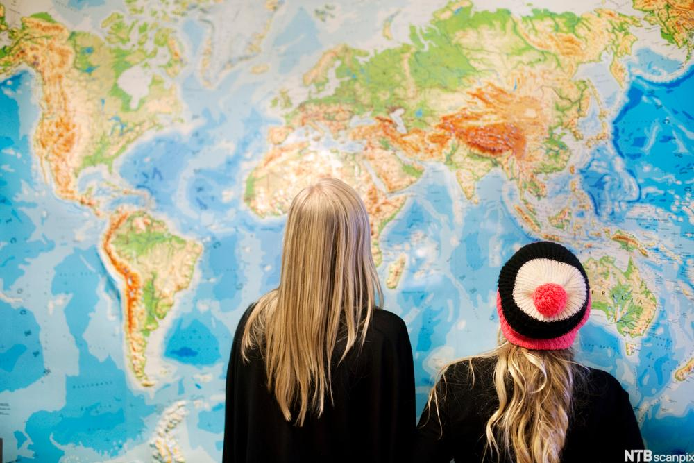 Two girls in front of a map of the world. Photo.