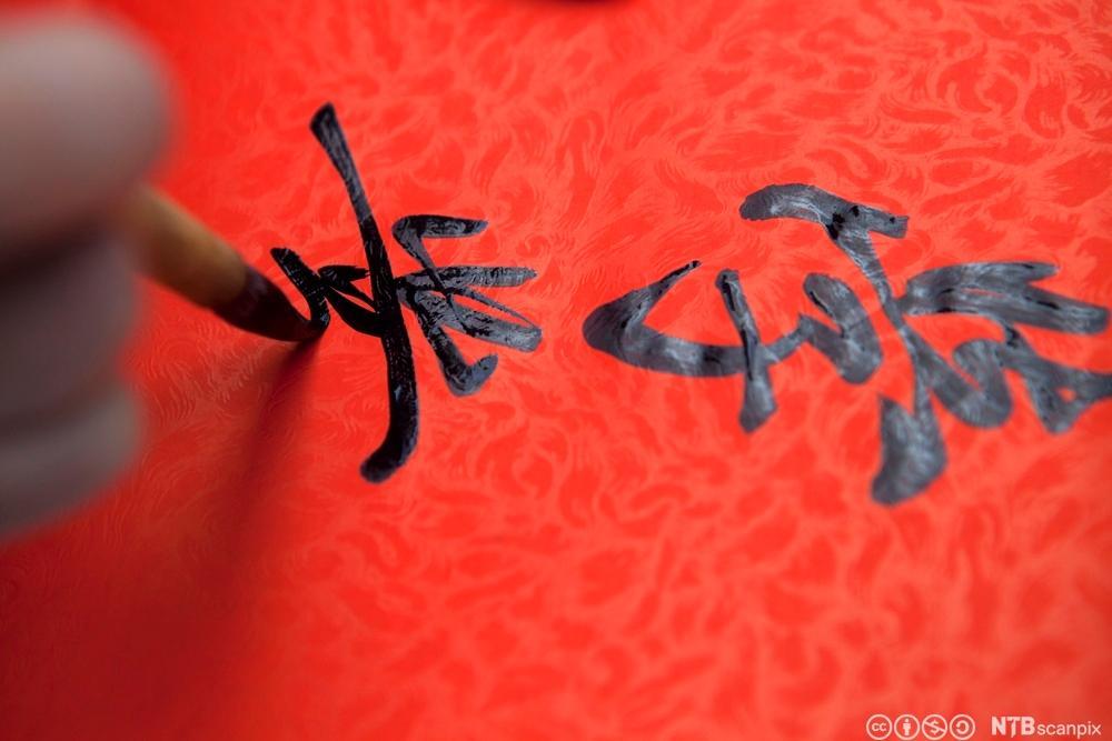En som skriver kinesiske tegn. Foto.