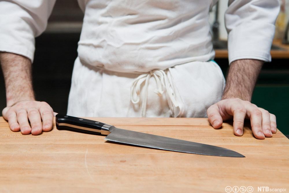 Ser hendene til ein mann som er klar for å kutte med kniv på ei skjerefjøl. Foto