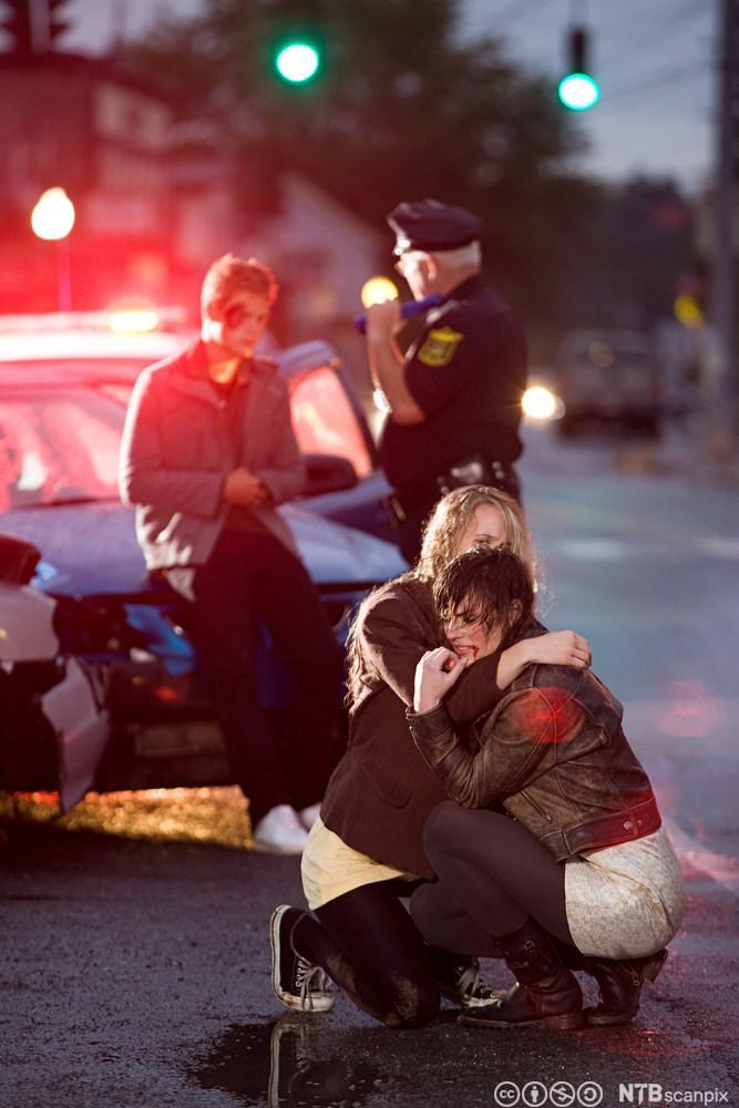 Et åsted for en bilulykke. To unge jenter holder rundt hverandre. Foto.
