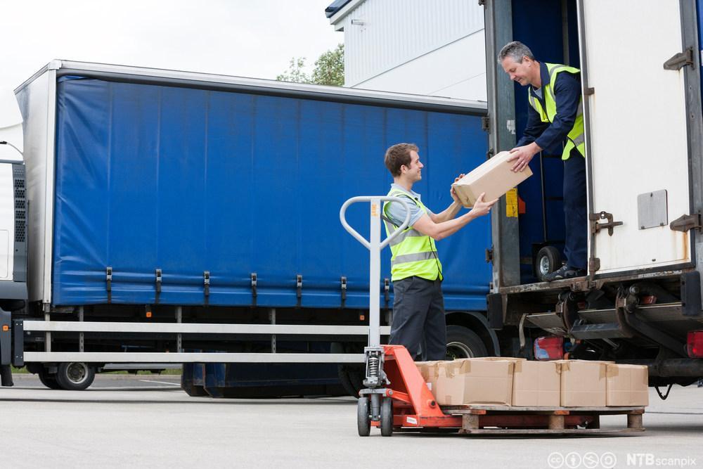 To menn losser varer fra en lastebil. Foto.