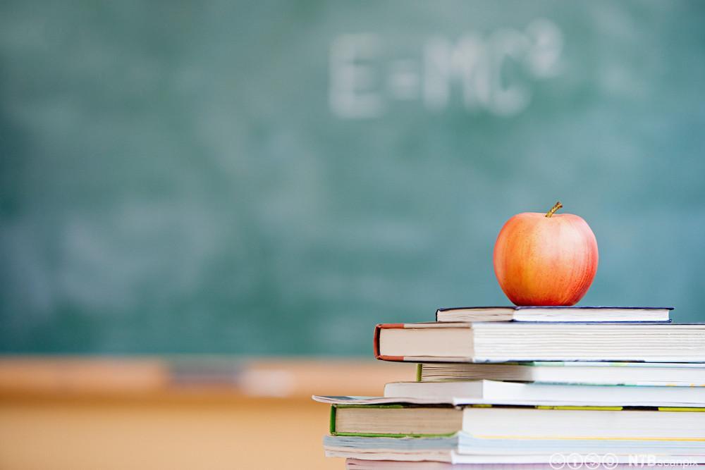 Skolebøker og eple i klasserom. Foto.