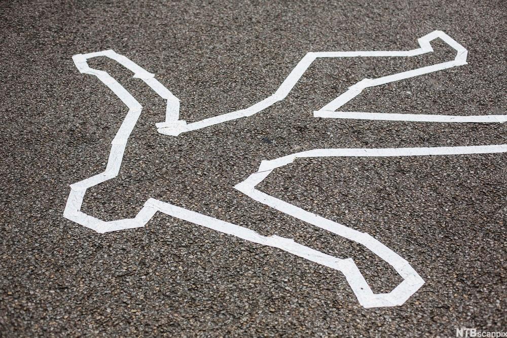 Hvitt omriss av kropp på asfalt