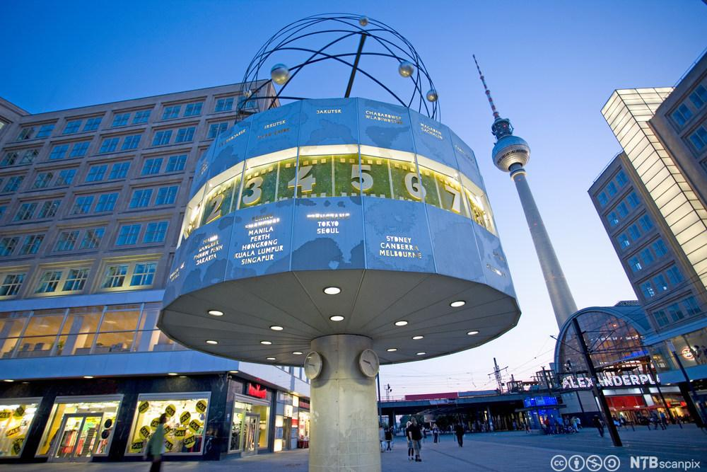 Bilde av Alexanderplatz i Berlin om kvelden. I forgrunnen et stort verdenstidsur, i bakgrunnen tv-tårnet. Foto.