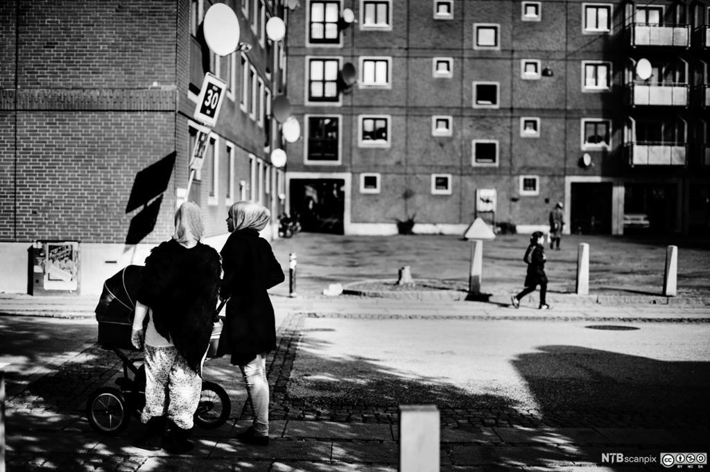 Muslimske kvinner med barnevogner står utenfor noen boligblokker. Foto.