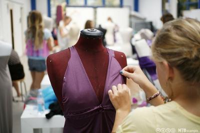 Klesdesigner som arbeider med en lilla kjole. Foto.