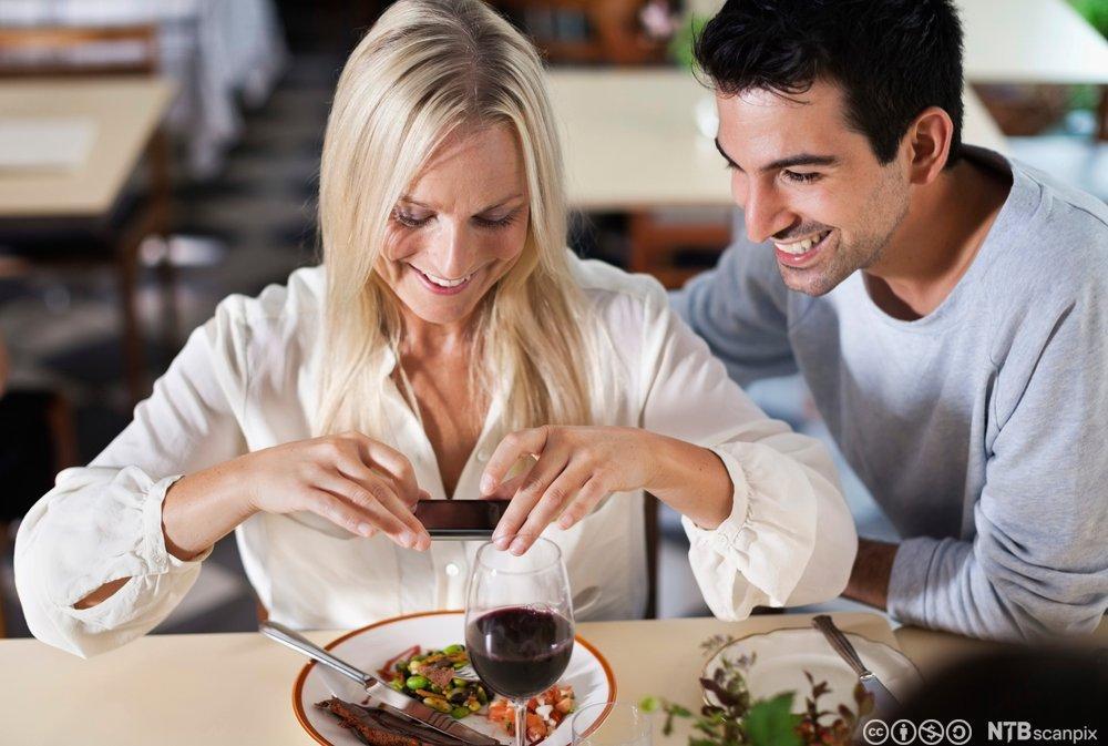 Gjester på en restaurant som tar bilde av maten. Foto.