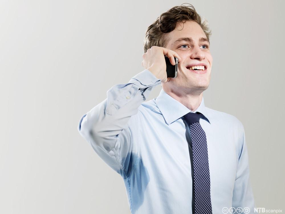 Ung mann snakker i mobiltelefon. Foto.