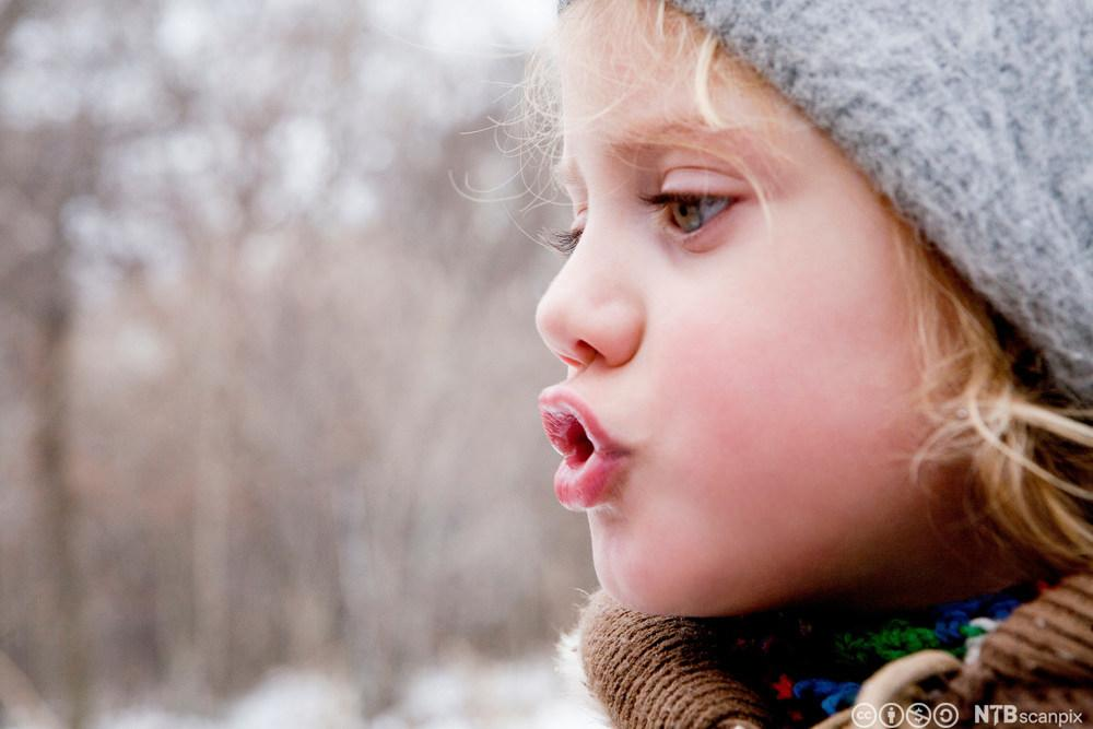 Liten jente som ser på pusten sin. Foto.
