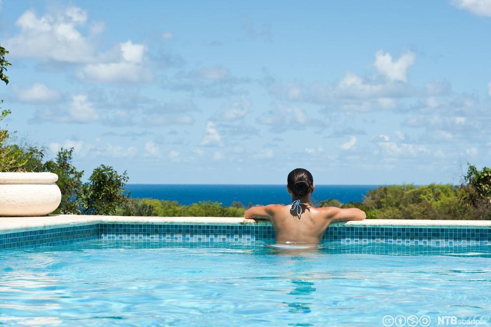 Kvinne i svømmebasseng ser mot horisonten. Foto.