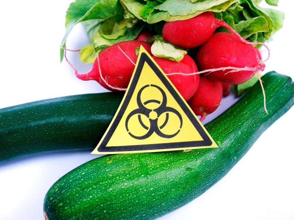Grønnsaker på en benk med et fareskilt. Foto.