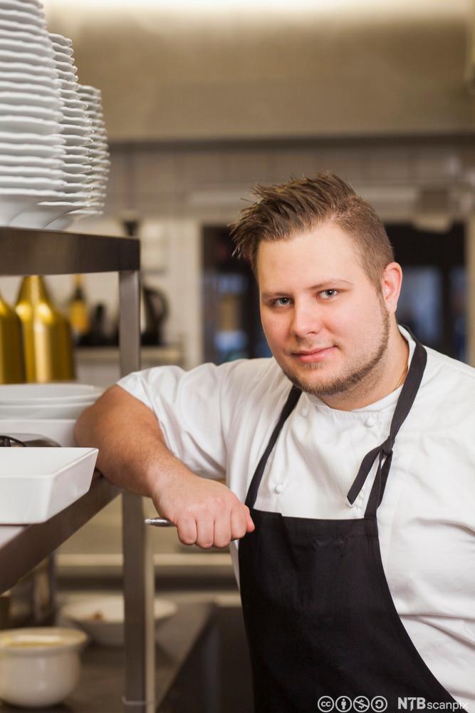 En ung, mannlig kokk på kjøkkenet. Foto.