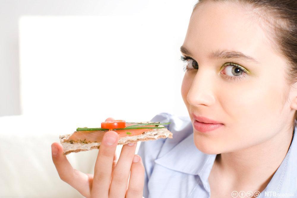 Ung dame som spiser et knekkebrød med røkt laks. Foto