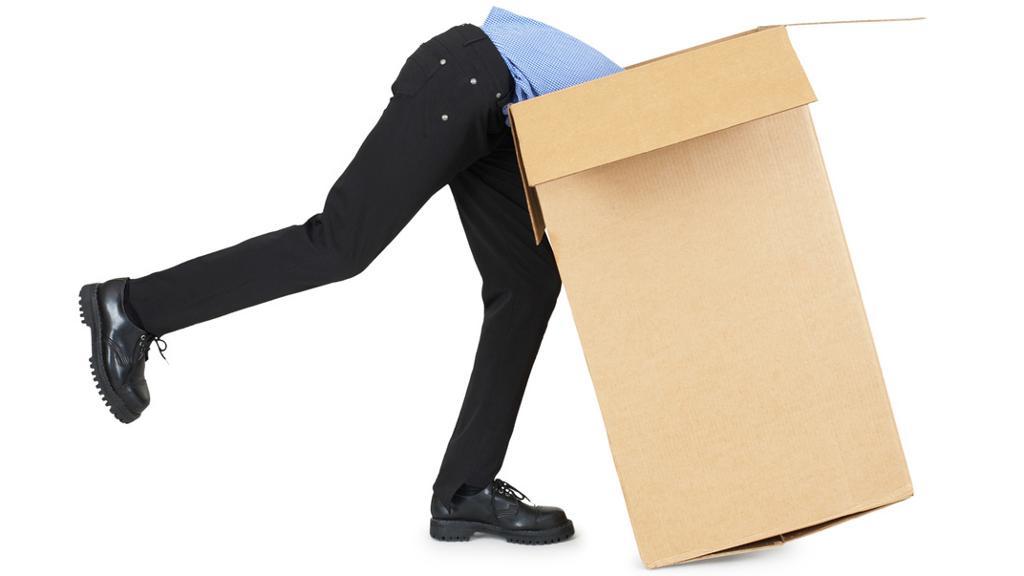 Mann klatrar inn i pappeske. Foto.