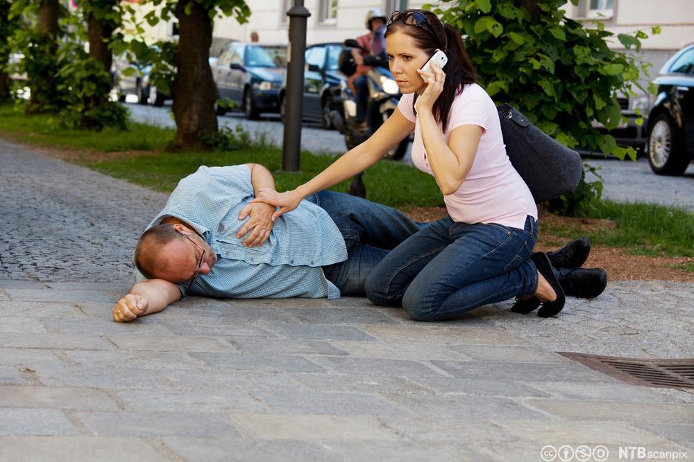 En mann ligger på bakken og holder på hjertet, mens en kvinne sitter på siden og ringer etter hjelp. Foto.