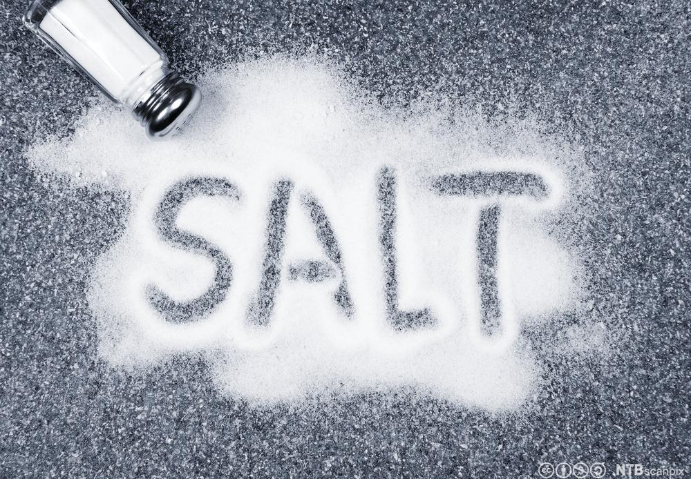 Salt skrevet med bokstaver i en haug med salt. Foto.