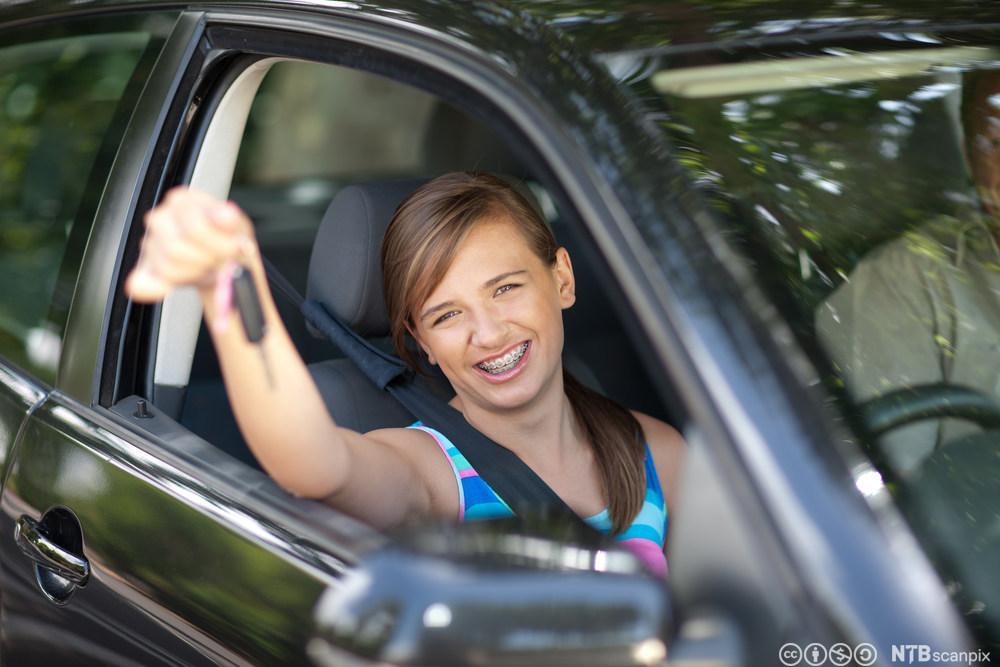 Jente holder nøkkel til ny bil. Foto.