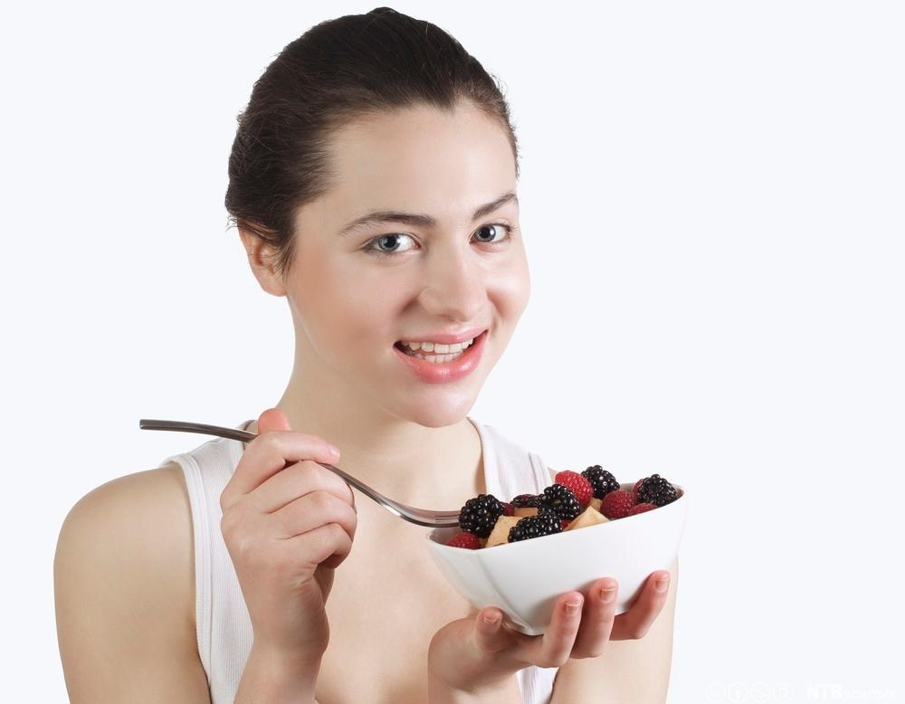 Ei ung dame et ein dessert med bjørnebær og jordbær. Foto.