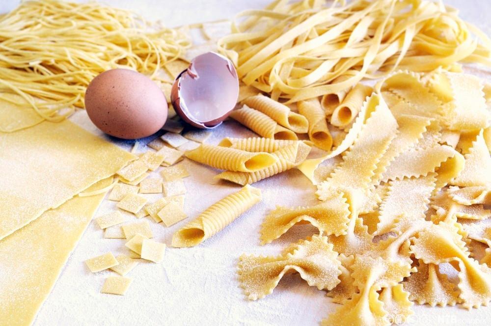 Ulike pastatyper og et egg på et bord. Foto.