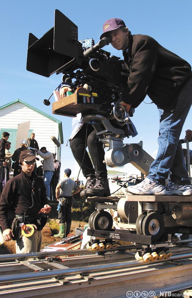 En mann kjører filmkamera på skinner. Fotografi.