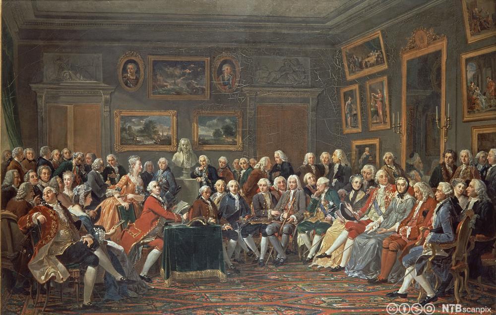 En samling av distingverte gjester i en salong hos Madame Geoffrin på 1700-tallet. Av gjestene er bl.a. Rousseau, Diderot og Montesquieu. Maleri.