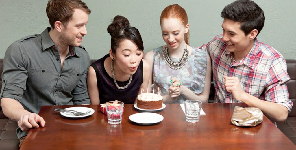 Bursdagsfeiring sammen med venner. En ung kvinne blåser ut lysene på en kake med tre smilende venner rundt seg. Foto.