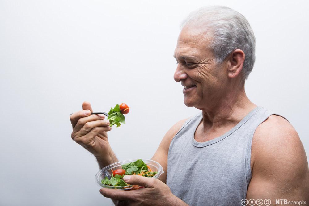 Mann som spiser salat. Foto