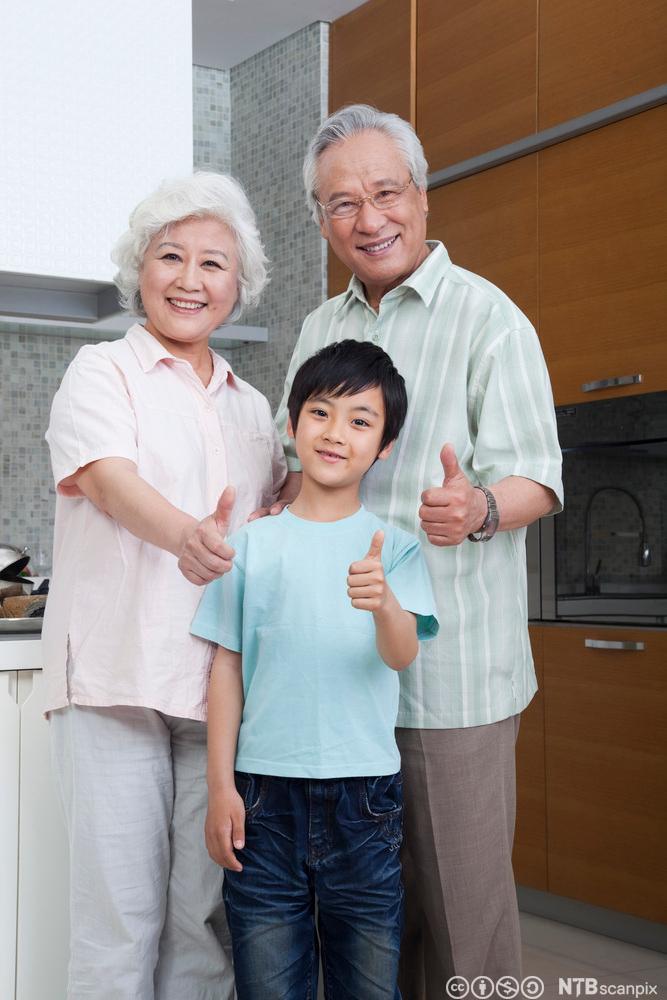 Kinesiske besteforeldre med barnebarn på kjøkkenet. Foto.