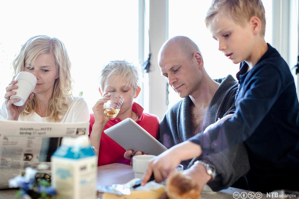 Mor, far og to gutter på 8 og 10 år sitter rundt frokostbordet og spiser. Foto.