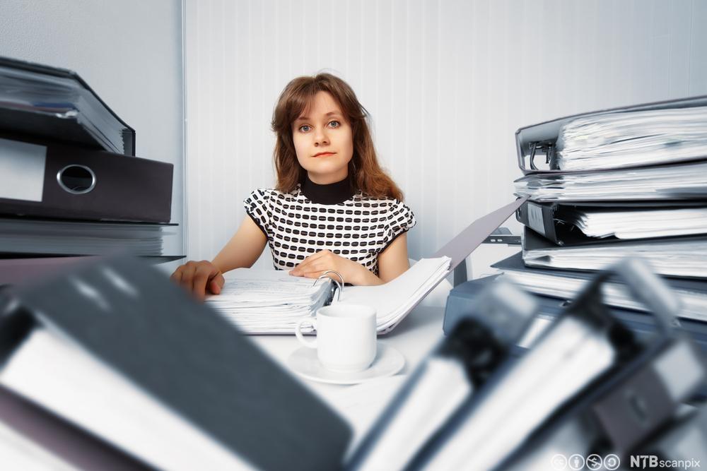 Regnskapsfører med mange permer på kontoret. Foto.