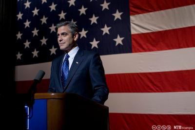 Mann i dress på talerstol. Det amerikanske flagget i bakgrunnen. Foto.