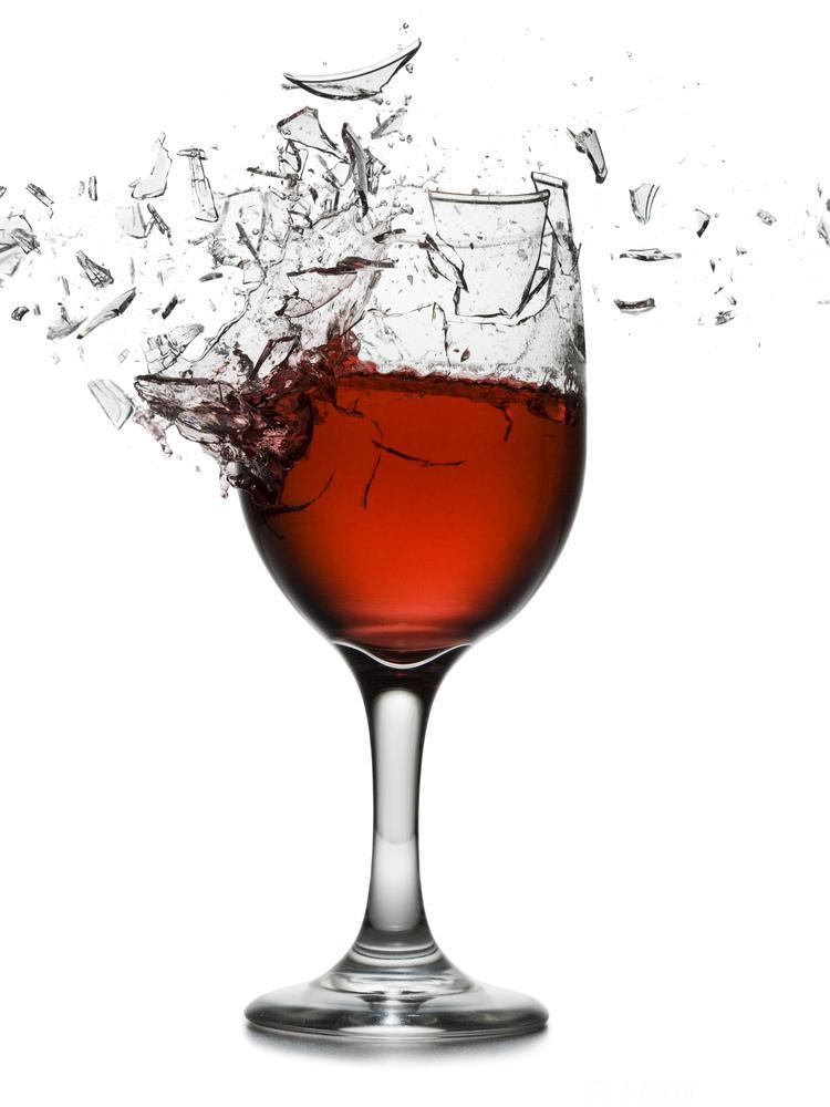 Et knust rødvinsglass. Foto.