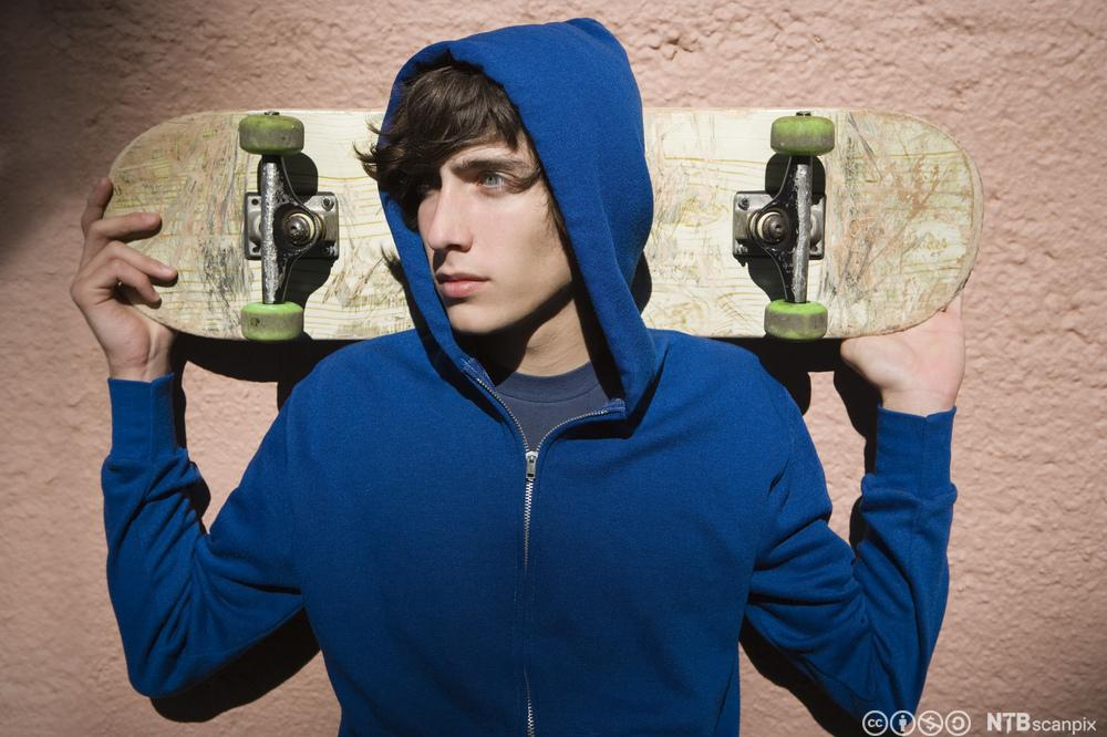 Gutt med skateboard og blå hettegenser. Foto.
