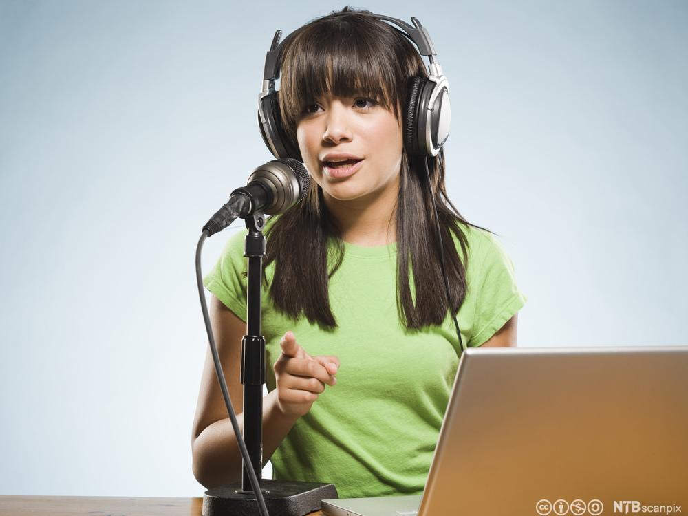 Jente med hodetelefoner og grønn T-skjorte sitter foran en datamaskin og snakker i mikrofon. Foto.