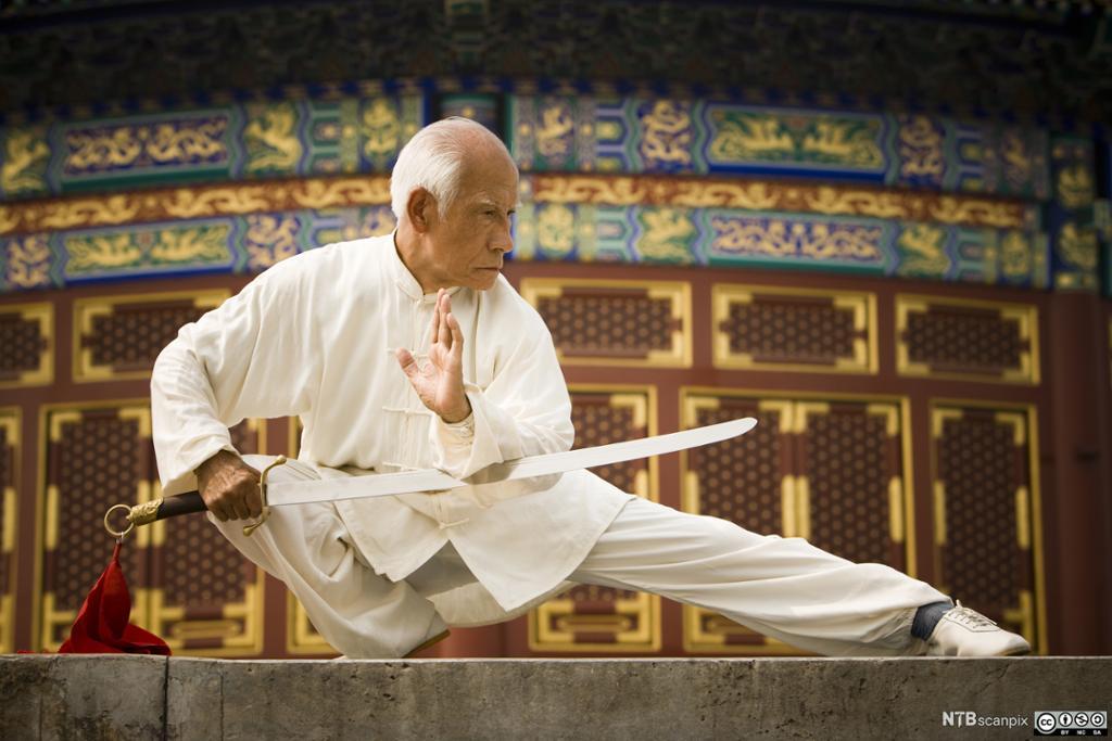 Eldre kinesisk mann trener Kung Fu med sverd. Foto.
