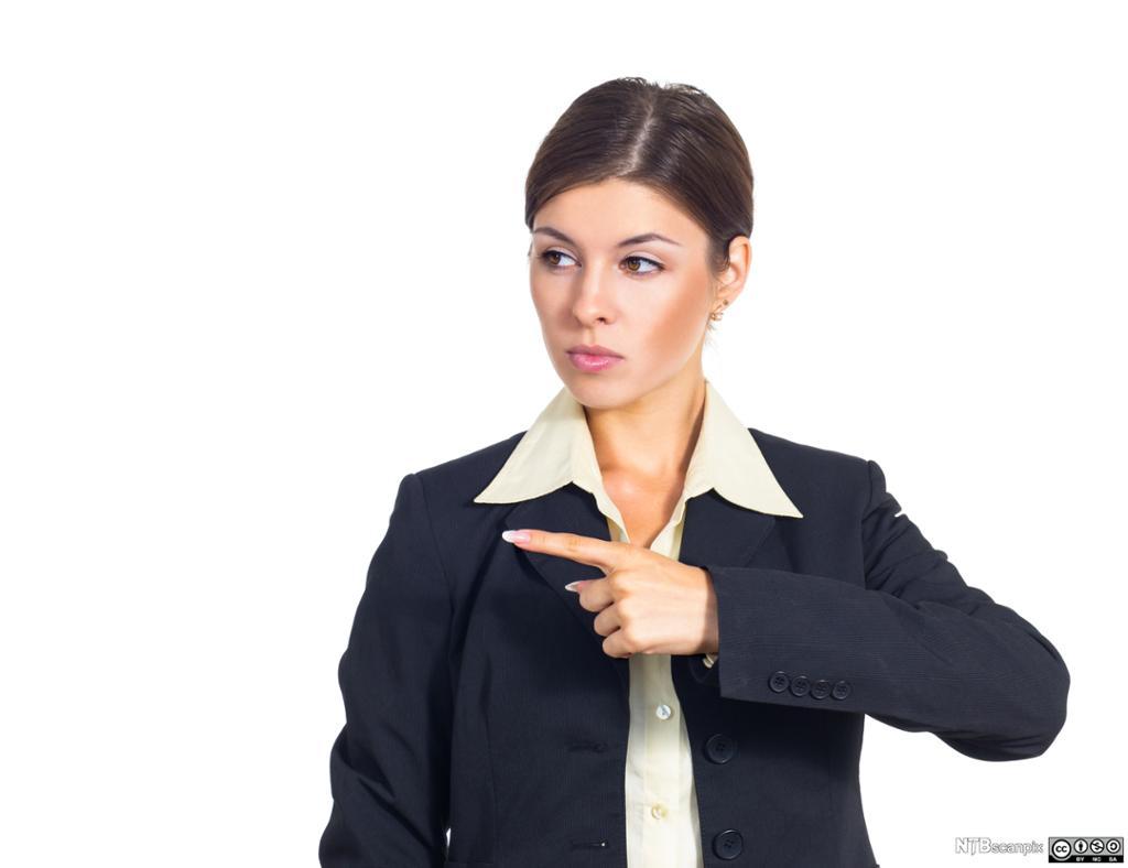 Kvinne peker mot venstre. Foto.