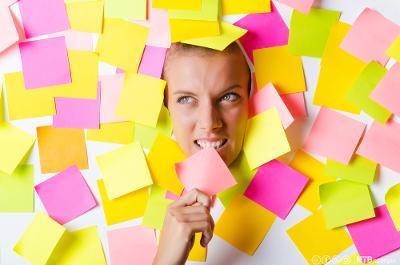 Voksen kvinne dekt til av gule og rosa post-it-lapper. Bare ansiktet og ei hand er synlig. Foto.