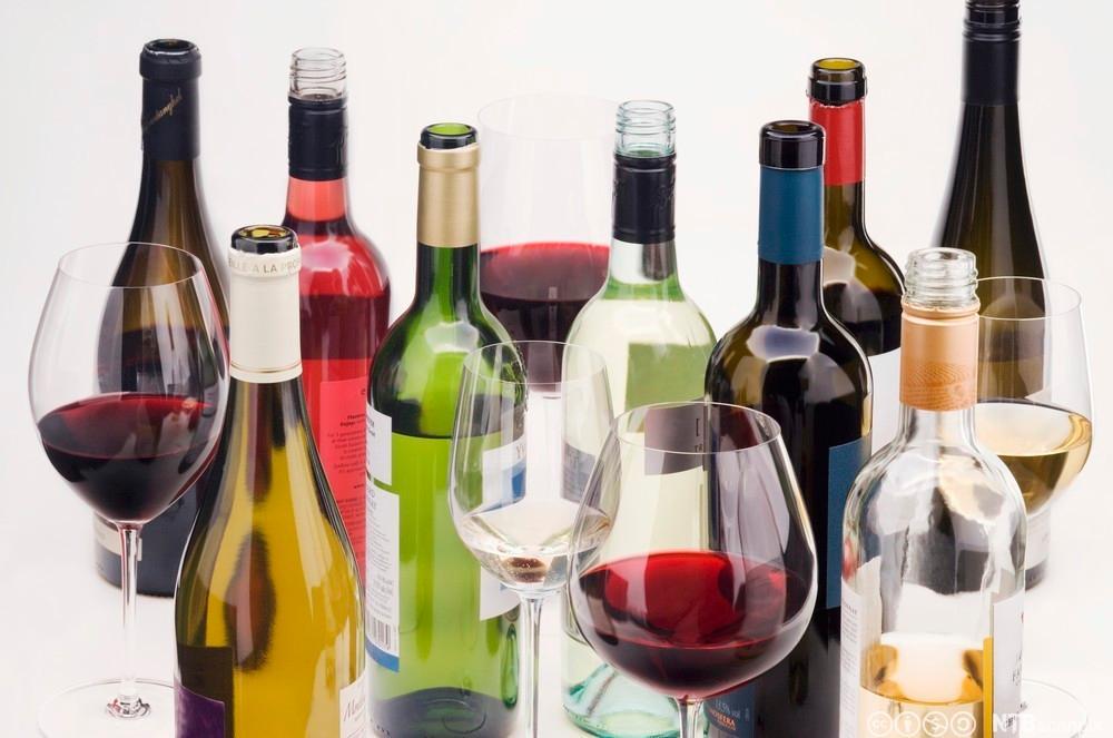 Vinflasker og glass med vin i mot hvit bakgrunn. Foto.