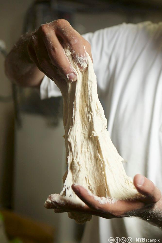 En baker som strekker ut en deig med mye gluten.Foto.