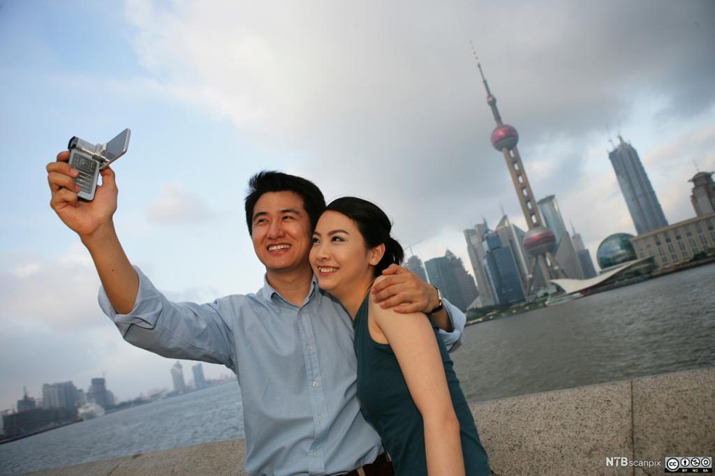 Et kinesisk par tar selfie fra Pudong med Shanghai i bakgrunnen. Foto.