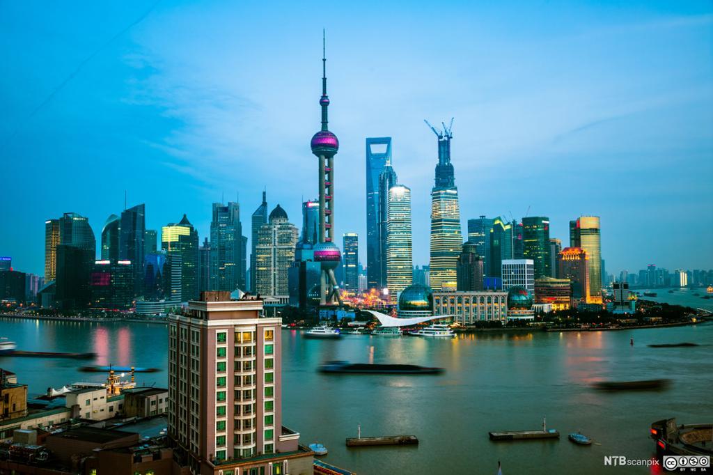 Shanghais skyskrapere i mange farger om kvelden. Foto.