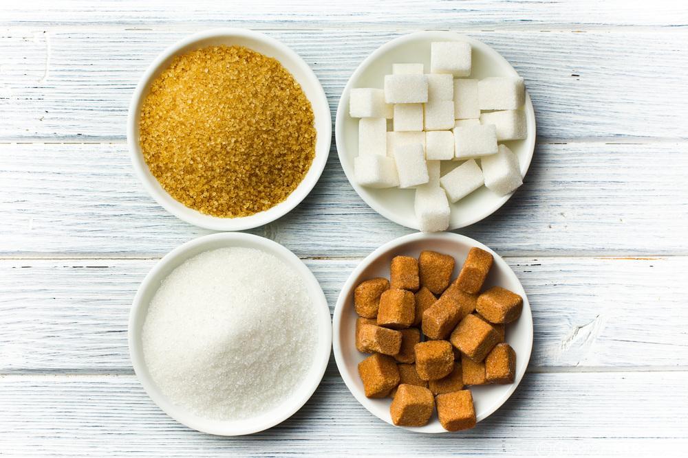 Brunt og kvitt sukker, laust og i bitar liggjande i skåler. Foto.