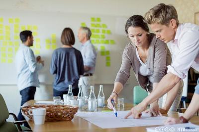 Fem personer i møteaktivitet. Tre av dem diskuterer foran ei tavle full av gule lapper, to av dem tegner på et stort ark. Foto.