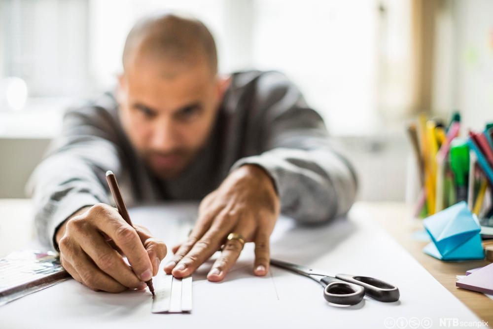 En mann som måler og tegner. Bilde.