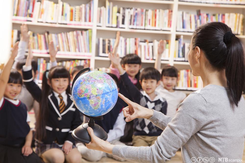 Kinesisk lærer viser elevene sine en globus. Foto.