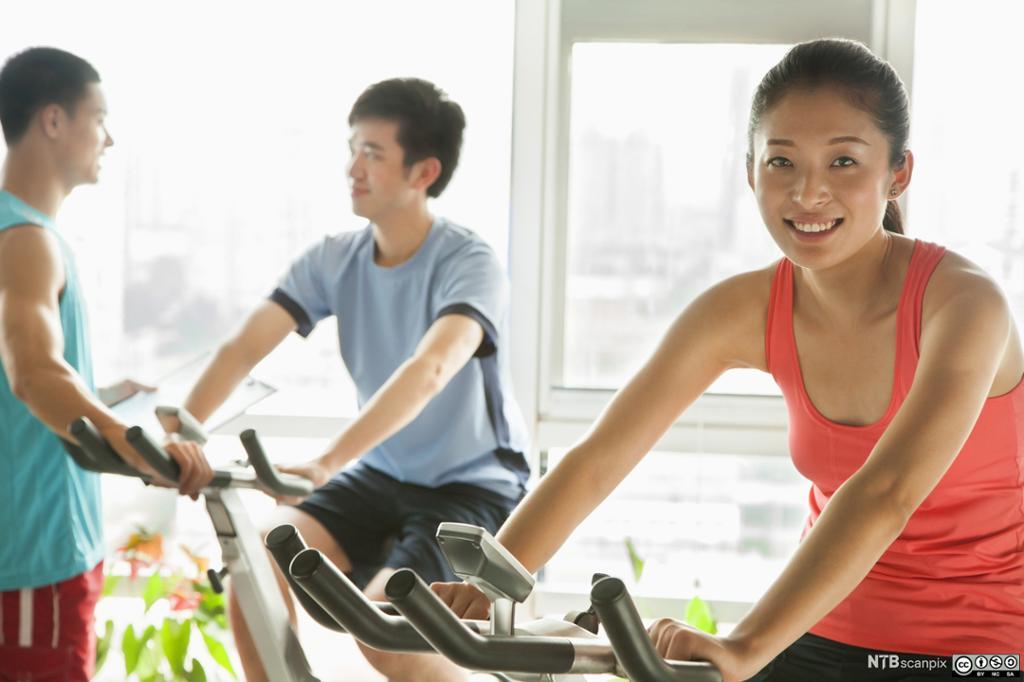 Unge mennesker på stasjonære sykler som trener i treningssenter Foto.