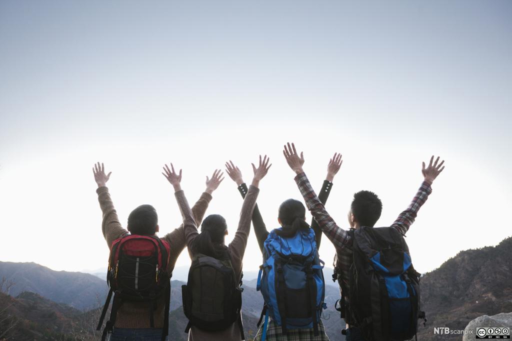 Turister strekker armene opp