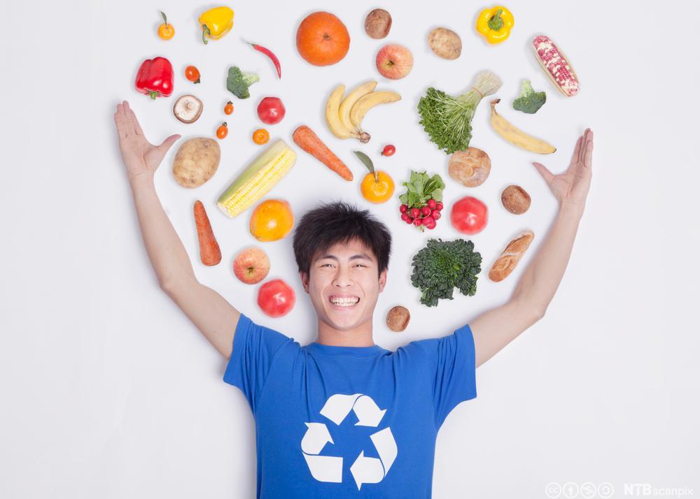 En ung mann holder grønnsakene opp og i lufta imellom dem svever det grønnsaker. Foto.