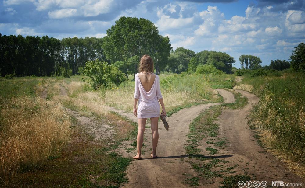 Ei jente med ryggen mot kamera står mellom to vegar som fører kvar sin veg. Foto.