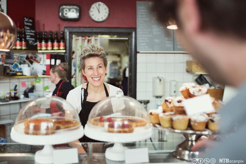 Bilete av ein smilande servitør bak ein kafedisk. Foto.
